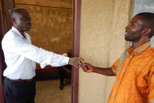 Un agent ISDD remet un bordereau au fermier avant d'entrer dans le bureau pour inscrire le nom du candidat qu'il souhaite voter