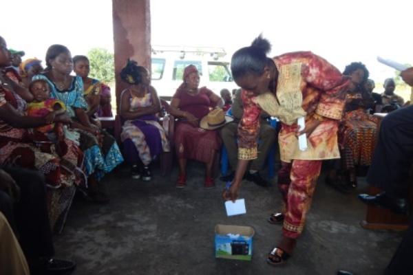Une fermière dépose son vote dans l'urne sous les yeux de toute l'assemblée